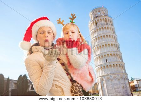 Mother In Christmas Hat And Daughter Giving Air Kiss In Pisa
