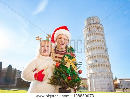 Happy Woman And Baby Girl Holding Christmas Tree. Pisa, Italy