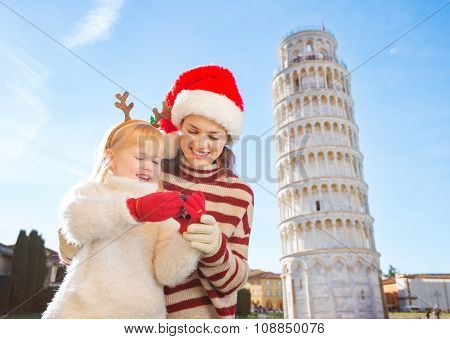 Mother In Christmas Hat And Daughter Checking Photos. Pisa