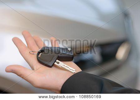 Car keys in salesclerks open hand.