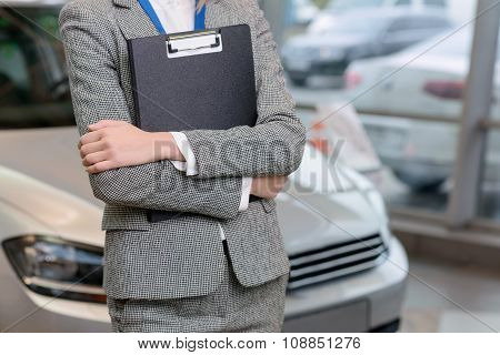 Saleswoman with clipboard is standing beside the car.