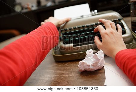 woman working on typewriter pulls paper out at table
