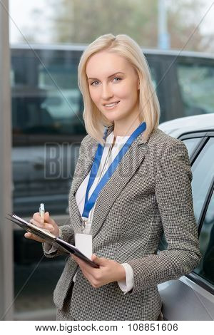 Saleswoman in car salon holding a clipboard.