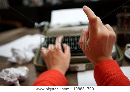 closeup of woman typing on old typewriter at table