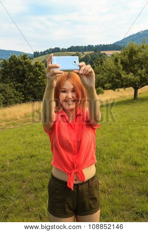 Young Woman Does Selfi In Nature In Summer