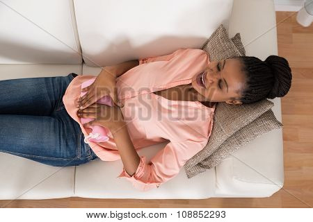Woman Lying On Sofa With Hot Water Bag