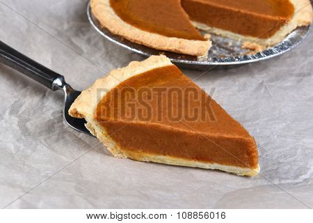Closeup of a slice of Pumpkin Pie on a spatula with the cut pie in the background.