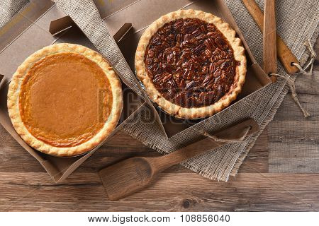 A pumpkin Pie and Pecan Pie in open bakery boxes on burlap and wood surface with wood utensils.