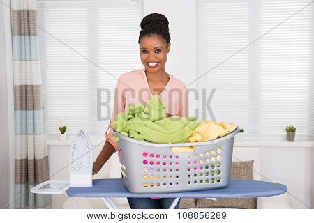 Woman With Iron And Clothes In Basket