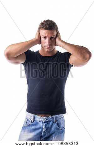 Attractive young man covering his ears, irritated