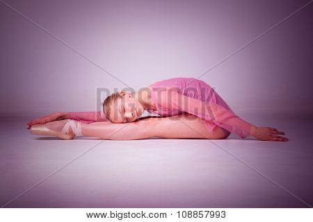 The young ballerina posing on the floor