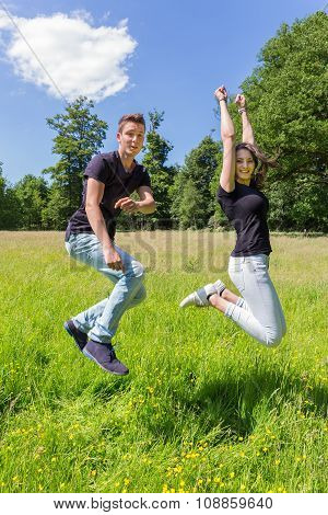 Young Dutch Couple Jumping In Green Meadow