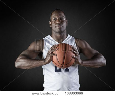 African American Basketball Player portrait holding a ball. Black background