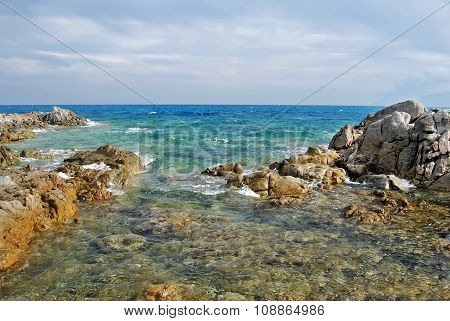 Sunny Coastal Landscape With Rocks, Agitated Sea And Cloudy Sky