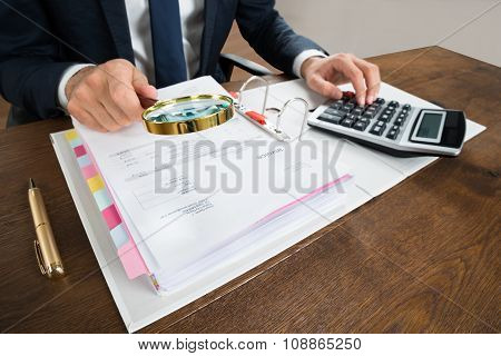 Businessman Checking Invoice With Magnifying Glass