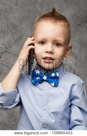 Portrait Of Little Boy In Blue Shirt And Bow Tie With Mobile Phone Against Gray Textural Background