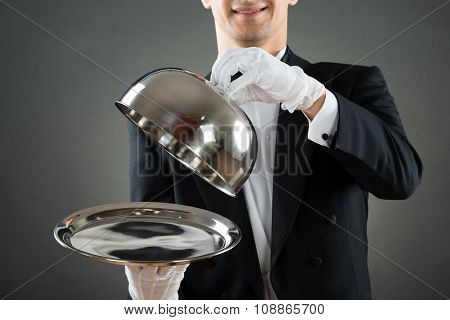 Midsection Of Waiter Holding Cloche Over Empty Tray