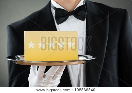 Midsection Of Waiter Holding Tray With Star Rating Label