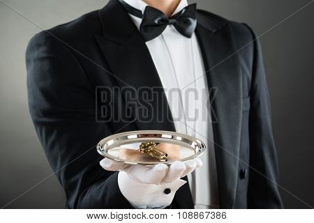Midsection Of Waiter Holding Tray With Keys