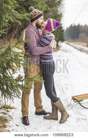 Young peaople are kissing in winter forest