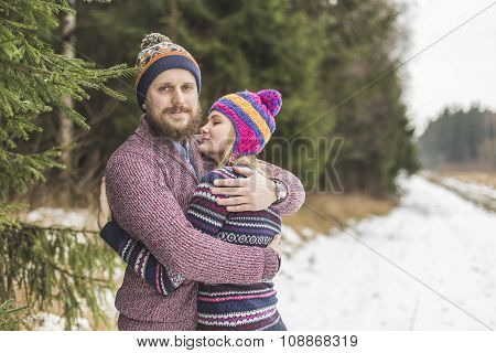 Young couple hugging in winter forest