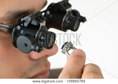 Jeweler Examining Diamond Ring With Magnifying Loupe