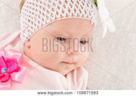 Portrait Of A Two-year Baby Girl With A Bandage On His Head With A Flower