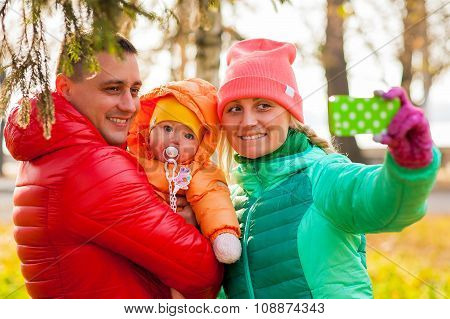 Young Family  Make Autumn Selfie With Their Kid