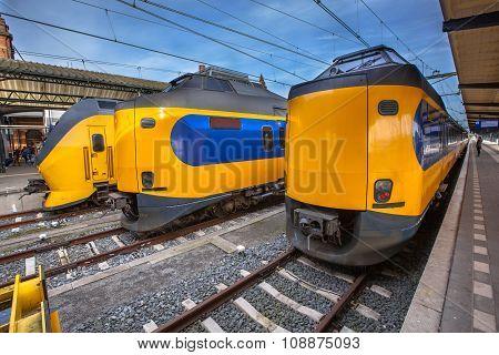 Three Modern Passenger Commuter Trains Waiting At A Historic Station