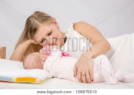 Mom Lovingly Watching Her Baby Lying On The Bed With Him