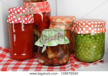 Jars with pickled vegetables on shelf