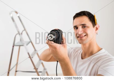 Portrait Of Smiling Man Holding Power Drill