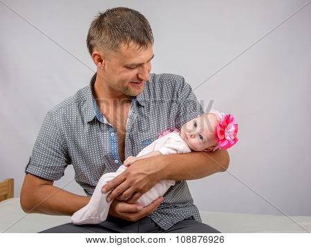 Joyful Father Holding Newborn Daughter And Looks At Her