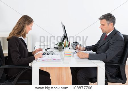 Businessman And Businesswoman Calculating Finance