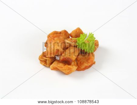 pile of pork greaves on white background