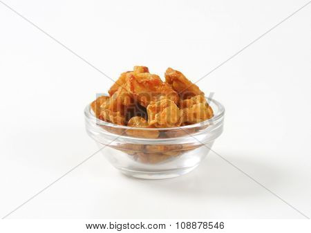 bowl of salty pork greaves on white background