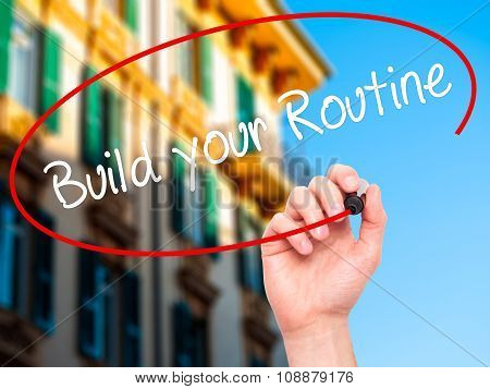 Man Hand writing Build your Routine with  marker on visual screen.