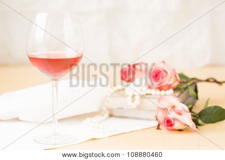 Glass Of Rose With Vintage Books And Pearls