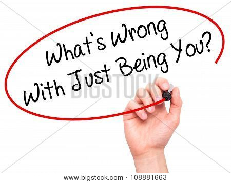 Man Hand writing What's Wrong With Just Being You? with black marker on visual screen.