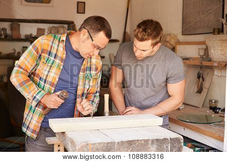 Stone Mason With Apprentice At Work On Carving In Studio