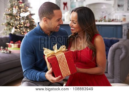 Romantic Couple Exchanging Christmas Gifts At Home