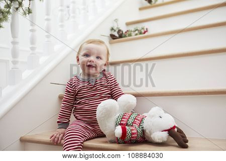 Young Girl On Stairs In Pajamas At Christmas
