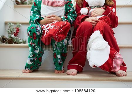 Two Children Sitting On Stairs With Christmas Stockings