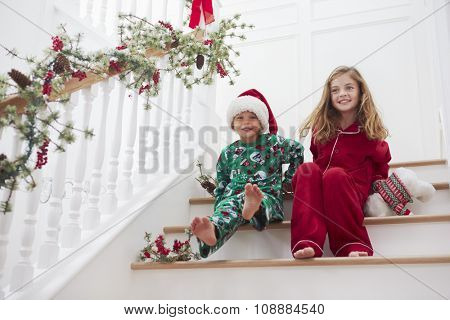 Two Children Sitting On Stairs In Pajamas At Christmas