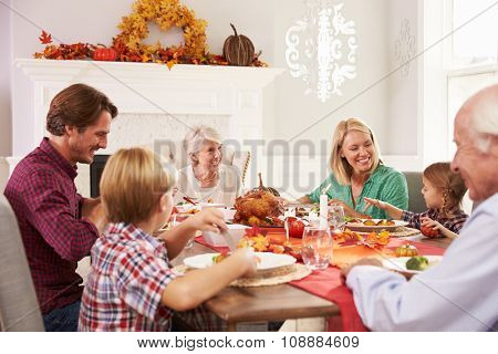 Family With Grandparents Enjoying Thanksgiving Meal At Table