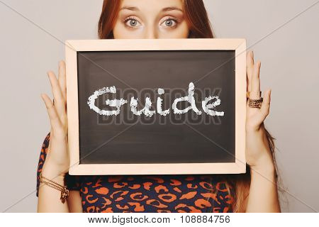 Young Woman Holding A Chalkboard Saying Guide