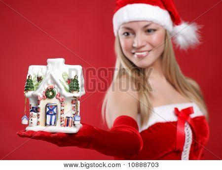 Uma jovem garota vestida como Papai Noel num fundo vermelho detém brinquedo um ano novo na palma