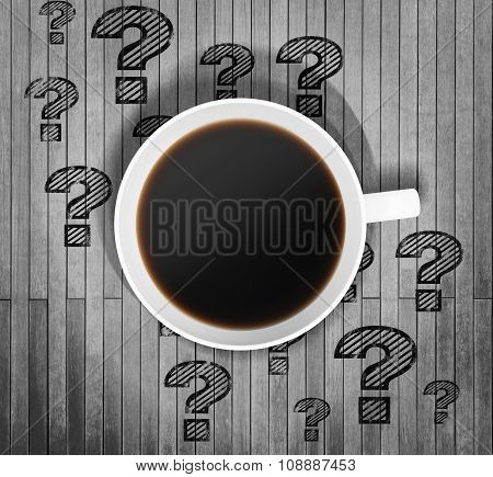 Top View Of A Cup Of Coffee And Drawn Question Marks Around It On The Wooden Table. 3D Rendering.