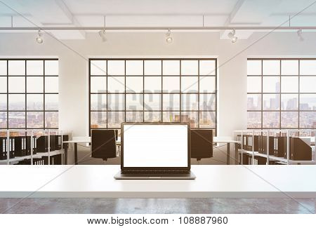 A Workplace In A Bright Modern Office. A Working Desk Is Equipped With A Modern Laptop With White Co