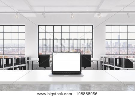 A Workplace In A Bright Modern Loft Open Space Office. A Working Desk Is Equipped With A Modern Lapt